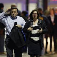 Photo - A man and woman leave the Garden State Plaza Mall with officials standing guard behind them following reports of a shooter, Monday, Nov. 4, 2013, in Paramus, N.J. Hundreds of law enforcement officers converged on the mall Monday night after witnesses said multiple shots were fired there. (AP Photo/Julio Cortez)