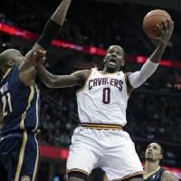 Photo - Cleveland Cavaliers' C.J. Miles (0) jumps to the basket against Indiana Pacers' David West (21) during the second quarter of an NBA basketball game on Friday, Dec. 21, 2012, in Cleveland. (AP Photo/Tony Dejak)