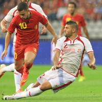Photo - Tunisia's Syam Ben Youssef, right, tries to tackle Belgium's Eden Hazard, during a friendly soccer match at the King Baudouin stadium in Brussels, Saturday, June 7, 2014. Belgium will play against South Korea, Russia and Algeria in Group H of the World Cup 2014 in Brazil. (AP Photo/Yves Logghe)
