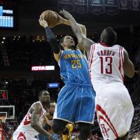 Photo - New Orleans Hornets shooting guard Austin Rivers (25) is fouled by Houston Rockets shooting guard James Harden (13) and power forward Patrick Patterson (54) while driving to the basket during the first half of an NBA basketball game on Wednesday, Jan. 2, 2013, in Houston.  (AP Photo/Bob Levey)