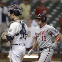 Photo - Washington Nationals' Ryan Zimmermann (11) crosses home after he hit a two-run home run against the Milwaukee Brewers during the 16th inning of a baseball game Wednesday, June 25, 2014, in Milwaukee. The Brewers' Jonathan Lucroy is at left. (AP Photo/Jeffrey Phelps)