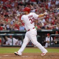 Photo - St. Louis Cardinals' Matt Adams hits an RBI double during the first inning of a baseball game against the Cincinnati Reds, Monday, Aug. 18, 2014, in St. Louis. (AP Photo/Scott Kane)