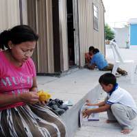 Photo - This Aug. 4, 2014 photo shows Eneyda Alvarez of Honduras peeling a mango while her son Antony plays at the Senda de Vida migrant shelter in Reynosa, Mexico. Alvarez hopes to join the thousands of families _ mothers or fathers with young children _ who have crossed the Rio Grande into the U.S. United States. (AP Photo/Christopher Sherman)