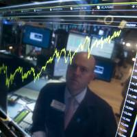 Photo - FILE - In this July 3, 2014 file photo, specialist Jay Woods is reflected in a screen at his post that shows five years of the Dow Jones industrial average, on the floor of the New York Stock Exchange. It's been a bad news summer, but you wouldn't know it from the way many investors have reacted. They've largely shrugged it off.  (AP Photo/Richard Drew, File)