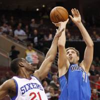 Photo - Dallas Mavericks' Dirk Nowitzki, right, of Germany shoots while being guarded by Philadelphia 76ers' Thaddeus Young, left, during the first half of an NBA basketball game, Friday, Feb. 21, 2014, in Philadelphia. (AP Photo/Chris Szagola)