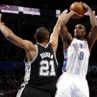 Photo - Oklahoma City's Serge Ibaka (9) shoots against San Antonio's Tim Duncan (21) during an NBA basketball game between the Oklahoma City Thunder and the San Antonio Spurs in Oklahoma City Monday, Dec. 17, 2012. Oklahoma City won, 107-93. Photo by Nate Billings, The Oklahoman