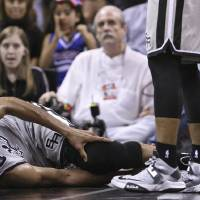 Photo - San Antonio Spurs' Tim Duncan lies on the floor after being injured on a play during the first half against the Washington Wizards during an NBA basketball game Saturday, Feb. 2, 2013, in San Antonio. The Spurs said via Twitter that Duncan sprained his right ankle and left knee and would not return to the game. (AP Photo/San Antonio Express-News, Edward A. Ornelas) SAN ANTONIO OUT