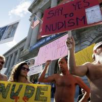Photo -   Demonstrators gather at a protest against a proposed nudity ban outside of City Hall in San Francisco, Wednesday, Nov. 14, 2012. San Francisco appears poised to shed part of its image as a city where anything goes, including clothing. The Board of Supervisors is scheduled to vote next week on a law that would ban public nudity. The proposal comes in response to a devoted group of nudists who proudly strut their stuff through the city's Castro District. (AP Photo/Marcio Jose Sanchez)