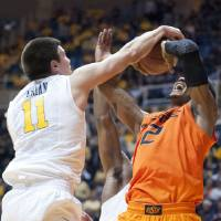 Photo - West Virginia's Nathan Adrian, left, blocks Oklahoma State's Le'Bryan Nash during the second half of an NCAA college basketball game Saturday, Jan. 11, 2014, in Morgantown, W.Va. Oklahoma State won 73-72. (AP Photo/Andrew Ferguson)