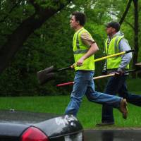 Photo - Workers with shovels run to the staging area for a rescue operation underway on the West Side of St. Paul, Minn.,  Wednesday, May 22, 2013. One child on a school field trip was killed and another remained unaccounted after a gravel slide Wednesday in a St. Paul park that's popular with children looking for fossils, authorities said.   (AP Photo/The St. Paul Pioneer Press, Scott Takushi)  MINNEAPOLIS STAR TRIBUNE OUT