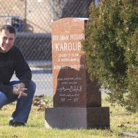 Photo - ADVANCE FOR USE SUNDAY, DEC. 30, 2012 AND THEREAFTER - This Dec. 18, 2012 photo shows Detroit Associated Press reporter Jeff Karoub next to the tombstone of his grandfather, The Rev. Imam Hussien Karoub, in Berkley, Mich. Wanting to fill some ancestral gaps, Jeff is piecing together the story of his grandfather who immigrated to America in 1912. (AP Photo/Carlos Osorio)