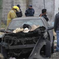 Photo - Hats belonging to victims sit on the hood of a damaged car as emergency workers gather a the scene where a truck loaded with fireworks exploded during a religious procession in the town of Nativitas, Mexico, Friday March 15, 2013. A truck loaded with fireworks exploded during a religious procession in this rural village in central Mexico, killing at least nine people and injuring dozens more, authorities said. (AP Photo/J. Guadalupe Perez)