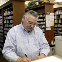 Photo - Mack D. Scherler fills prescriptions at the Medicine Cabinet in Oklahoma City.  PHOTO BY SARAH PHIPPS, THE OKLAHOMAN