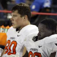 Photo -   Oklahoma State defensive ends Ryan Robinson (96) and Cooper Bassett (80) can only watch as Arizona's offensive scores another touchdown during the second half of an NCAA college football game at Arizona Stadium in Tucson, Ariz., Sat., Sept. 8, 2012. (AP Photo/Wily Low)