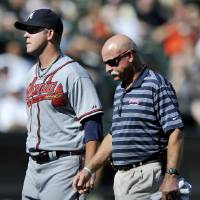 Photo - Atlanta Braves starting pitcher Paul Maholm left, walks to the dugout with a trainer after being pulled during the fourth inning of an interleague baseball game against the Chicago White Sox in Chicago, Saturday, July 20, 2013. (AP Photo/Paul Beaty)
