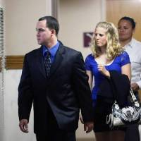 Photo - Dusten Brown, left, and his wife Robin enter the courtroom, Wednesday, Sept. 4, 2013 at the Muskogee County Courthouse in Muskogee, Okla. Oklahoma Gov. Mary Fallin on Wednesday signed an extradition order to send the father of a Cherokee girl in the middle of a custody dispute to South Carolina to face a criminal charge for refusing to hand his 3-year-old daughter over to her adoptive parents. (AP Photo/Tulsa World, Matt Barnard)