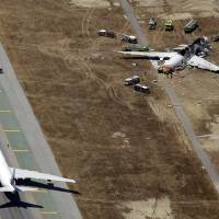 Photo - In this Saturday, July 6, 2013 aerial photo, emergency crews respond at the scene of the wreckage of Asiana Flight 214, top right, after it crashed at the San Francisco International Airport in San Francisco, earlier in the day. The pilot at the controls of airliner had just 43 hours of flight time in the Boeing 777 and was landing one for the first time at San Francisco International. (AP Photo/Marcio Jose Sanchez)