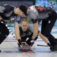 Photo - Canada's skip Brad Jacobs, center, delivers the rock to his sweepers Ryan Harnden, left, and E.J. Harnden during men's curling competition against Norway at the 2014 Winter Olympics, Friday, Feb. 14, 2014, in Sochi, Russia. (AP Photo/Robert F. Bukaty)