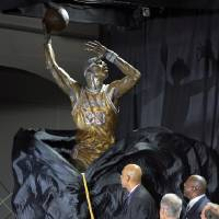 Photo -   Former Los Angeles Lakers center Kareem Abdul-Jabbar, left, unveils a statue of himself in front of Staples Center as Earvin