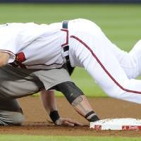 Photo - Atlanta Braves second baseman Phil Gosselin, right, falls onto Oakland Athletics' Jonny Gomes (15) after the pickoff at second base during the first inning of a baseball game against the Oakland Athletics Friday, Aug. 15, 2014, in Atlanta. The play was reviewed and the call was upheld for an out. (AP Photo/David Tulis)