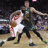 Photo - Houston Rockets's James Harden (13) tries to get past Utah Jazz's Gordon Hayward (20) in the first half of an NBA basketball game Monday, March 17, 2014, in Houston. (AP Photo/Pat Sullivan)