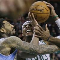 Photo - Boston Celtics forward Paul Pierce, right, goes to the hoop against Denver Nuggets guard Wilson Chandler, left, during the first half of an NBA basketball game in Boston, Sunday, Feb. 10, 2013. (AP Photo/Elise Amendola)
