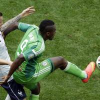 Photo - France's Mathieu Debuchy, left, and Nigeria's Emmanuel Emenike challenge for the ball during the World Cup round of 16 soccer match between France and Nigeria at the Estadio Nacional in Brasilia, Brazil, Monday, June 30, 2014. (AP Photo/Hassan Ammar)