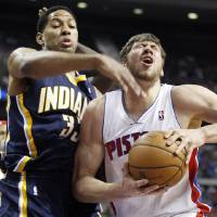 Photo - Detroit Pistons center Viacheslav Kravtsov, right, gets hit in the eye by Indiana Pacers forward Danny Granger, left, while going to the basket in the first half of an NBA basketball game Saturday, Feb. 23, 2013, in Auburn Hills, Mich. Granger was called for a foul on the play. (AP Photo/Duane Burleson)