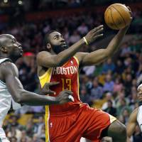 Photo - Houston Rockets' James Harden (13) goes up to shoot past Boston Celtics' Kevin Garnett (5) as Paul Pierce, right, watches during the first quarter of an NBA basketball game in Boston, Friday, Jan. 11, 2013. (AP Photo/Michael Dwyer) ORG XMIT: MAMD101