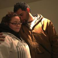 Photo - A couple embraces as they participate in a prayer meeting at the Heaven Ice Cream shop, Friday, Dec. 14, 2012 in Newtown, Conn. A gunman walked into the school Friday and opened fire, killing 26 people, including 20 children.  (AP Photo/Mary Altaffer)