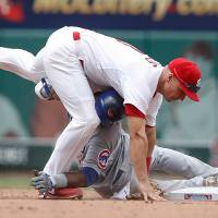 Photo - St. Louis Cardinals second baseman Mark Ellis, top, and Chicago Cubs'  Junior Lake collide as Ellis tags him out at second base during the sixth inning of a baseball game Thursday, May 15, 2014, in St. Louis. (AP Photo/Sarah Conard)