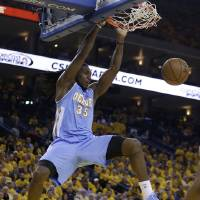 Photo - Denver Nuggets' Kenneth Faried (35) scores against the Golden State Warriors during the first half of Game 3 in a first-round NBA basketball playoff series on Friday, April 26, 2013, in Oakland, Calif. (AP Photo/Ben Margot)