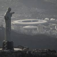 Photo - In this May 13, 2014, photo,This aerial view shot through an airplane window shows the Maracana stadium behind the Christ the Redeemer statue in Rio de Janeiro, Brazil. As opening day for the World Cup approaches, people continue to stage protests, some about the billions of dollars spent on the World Cup at a time of social hardship, but soccer is still a unifying force. The international soccer tournament will be the first in the South American nation since 1950. (AP Photo/Felipe Dana, File)