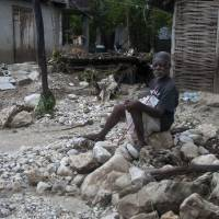 Photo -   A man sits in front of his home, on debris left by a flood caused by the heavy rains from Hurricane Sandy in Gran Goave, Haiti, Friday, Oct. 26, 2012. The hurricane raged through the Bahamas early Friday after leaving 38 people dead across the Caribbean. The death toll was still rising in Haiti, reaching 25 on Friday as word of disasters reached officials and rains continued to fall. (AP Photo/Dieu Nalio Chery)