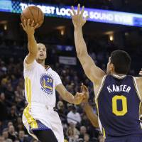 Photo - Golden State Warriors shooting guard Stephen Curry (30) shoots against Utah Jazz center Enes Kanter (0) during the first quarter of an NBA basketball game in Oakland, Calif., Saturday, Nov. 16, 2013. (AP Photo/Jeff Chiu)