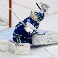 Photo - Vancouver Canucks' goalie Roberto Luongo makes a glove save against the Chicago Blackhawks during the second period of an NHL hockey game in Vancouver, British Columbia, on Friday, Feb. 1, 2013. (AP Photo/The Canadian Press, Darryl Dyck)