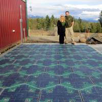 Photo - In this May 2014, photo provided by Solar Roadways, Scott and Julie Brusaw stand for a photo on a prototype solar-panel parking area at their company's business in Sandpoint, Idaho. Scott Brusaw's idea for solar-powered roads has gone viral and raised more than $1.4 million in crowdsourced funding. Brusaw is proposing to pave driveways, parking lots, bike trails and, eventually, highways with hexagon-shaped solar panels that will produce electricity and could even propel electric cars. (AP Photo/Solar Roadways)