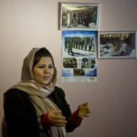 Photo - In this Wednesday, March 5, 2014 photo, prominent Afghan women's rights activist Wazhma Frogh stands next to pictures of female Afghan police officers she trains, in her office in Kabul, Afghanistan. A gender and development specialist and human rights activist, Frogh says her experience characterizes the women's rights movement in her country- after 12 years, billions of dollars and countless words emanating from the West commiserating with Afghan women, the successes are fragile, the changes superficial and vulnerable.  (AP Photo/Anja Niedringhaus)