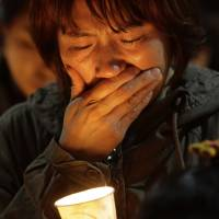 Photo - A woman offers prayers during a candlelight vigil for the missing passengers of a sunken ferry at Danwon High School in Ansan, South Korea, Thursday, April 17, 2014. An immediate evacuation order was not issued for the ferry that sank off South Korea's southern coast, likely with scores of people trapped inside, because officers on the bridge were trying to stabilize the vessel after it started to list amid confusion and chaos, a crew member said Thursday.  (AP Photo/Wonghae Cho)