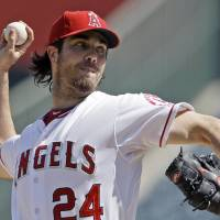 Photo - FILE - In this Sept. 27, 2012, file photo, Los Angeles Angels starter Dan Haren pitches to the Seattle Mariners in the second inning of a baseball game in Anaheim, Calif. A person familiar with the talks tells The Associated Press on Tuesday, Dec. 4, 2012, that the free agent pitcher and the Washington Nationals are close to completing a one-year deal for $13 million. (AP Photo/Reed Saxon, File)