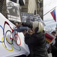 Photo - Activist Ann Northrop is joined by demonstrators from Queer Nation, and others who oppose the Russian government's continued attacks on human rights, including the rights of LGBT Russians, as she pours fake blood on an Olympic flag, marking the start of the 2014 Winter Olympic Games with a protest, outside the Consulate General of the Russian Federation, in New York,  Thursday, Feb. 6, 2014. (AP Photo/Richard Drew)
