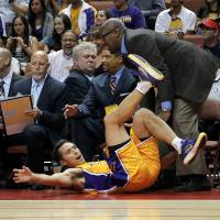 Photo -   Los Angeles Lakers' Steve Nash, bottom, collides with head coach Mike Brown as he goes after a loose ball during the first half of an NBA preseason basketball game against the Utah Jazz in Anaheim, Calif., Tuesday, Oct. 16, 2012. (AP Photo/Jae Hong)