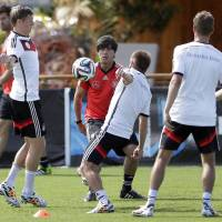Photo - German national soccer team head coach Joachim Loew, background center, plays soccer with team members Toni Kroos, left, Philipp Lahm and Miroslav Klose during a training session in Santo Andre near Porto Seguro, Brazil, Saturday, June 14, 2014. Germany will play in group G of the 2014 soccer World Cup. (AP Photo/Matthias Schrader)