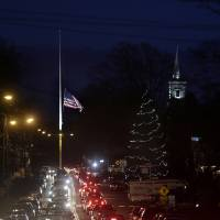Photo - Under a flag at half-staff and a Christmas tree, traffic piles up along a main road in Newtown, Conn., Thursday, Dec. 20, 2012. (AP Photo/Seth Wenig)