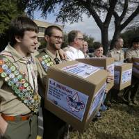 Photo - FILE - In this Feb. 4, 2013 file photo, James Oliver, left, hugs his brother and fellow Eagle Scout, Will Oliver, who is gay, as Will and other supporters carry four boxes filled with petitions to end the ban on gay scouts and leaders in front of the Boy Scouts of America headquarters in Dallas, Texas. With its ranks deeply divided, the Boy Scouts of America is asking its local leaders from across the country to decide whether its contentious membership policy should be overhauled so that openly gay boys can participate in Scout units. The proposal to be put before the roughly 1,400 voting members of the BSA's National Council on Thursday, May 23, 2013 at a meeting in Grapevine, Texas, would retain the Scouts' long-standing ban on gays serving in adult leadership positions. (AP Photo/Tony Gutierrez, File)
