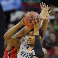 Photo - Oklahoma State forward Le'Bryan Nash (2) passes to a teammate while covered by Texas Tech forward Jordan Tolbert, back, during the first half of an NCAA college basketball game in the Big 12 men's tournament in Kansas City, Mo., Wednesday, March 12, 2014. (AP Photo/Orlin Wagner)