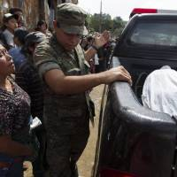 Photo - A woman watches as bodies of victims of an attack are taken away by police in San Jose Nacahuil, on the outskirts of Guatemala City, Sunday, Sept. 8, 2013. Men firing from a car poured gunshots into three cantinas in this rural town, killing at least 10 people and injuring 19, local firefighters said Sunday. (AP Photo/Moises Castillo)