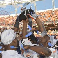 Photo - In this photo taken on Sunday, Jan. 19, 2014, Denver Broncos cornerback Champ Bailey, right, and teammates celebrate with the Lamar Hunt trophy after thy defeated the New England Patriots 26-16 in the AFC Championship NFL football game in Denver. Bailey finally gets a chance to live up to his name. The 12-time Pro Bowler is headed to his first Super Bowl in his 15th — and most trying — NFL season, one in which he missed 11 games and parts of two others because of a nagging foot injury. (AP Photo/Jack Dempsey)