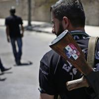 Photo - FILE - This Aug. 21, 2013 file photo shows a Syrian military soldier holding his AK-47 with a sticker of Syrian President Bashar Assad and Arabic that reads,
