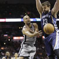 Photo - San Antonio Spurs' Tony Parker (9), of France, passes the ball around Memphis Grizzlies' Marc Gasol (33), of Spain, during the second half on an NBA basketball game, Wednesday, Oct. 30, 2013, in San Antonio. (AP Photo/Eric Gay)